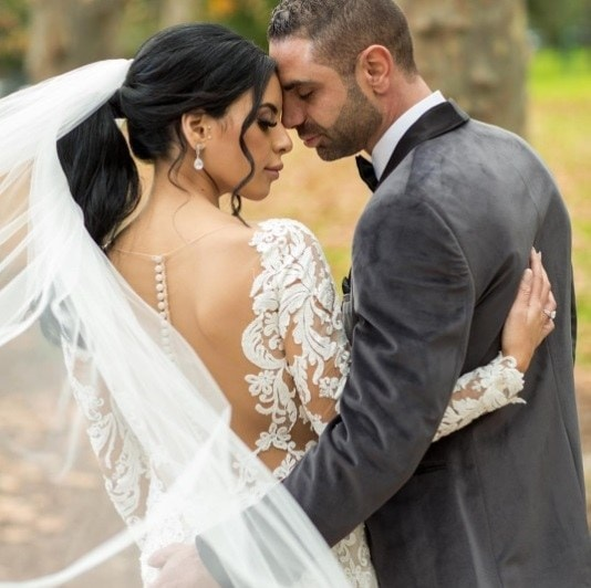 brunette bride with her hair in a ponytail standing with her husband