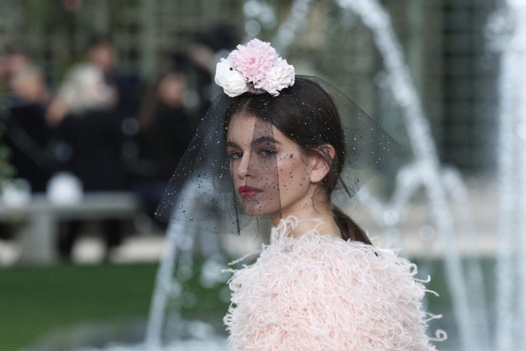 close up shot of kaia gerber with low sleek ponytail with floral viell on it, wearing pink fluffly dress on the chanel paris haute couture runway ss18