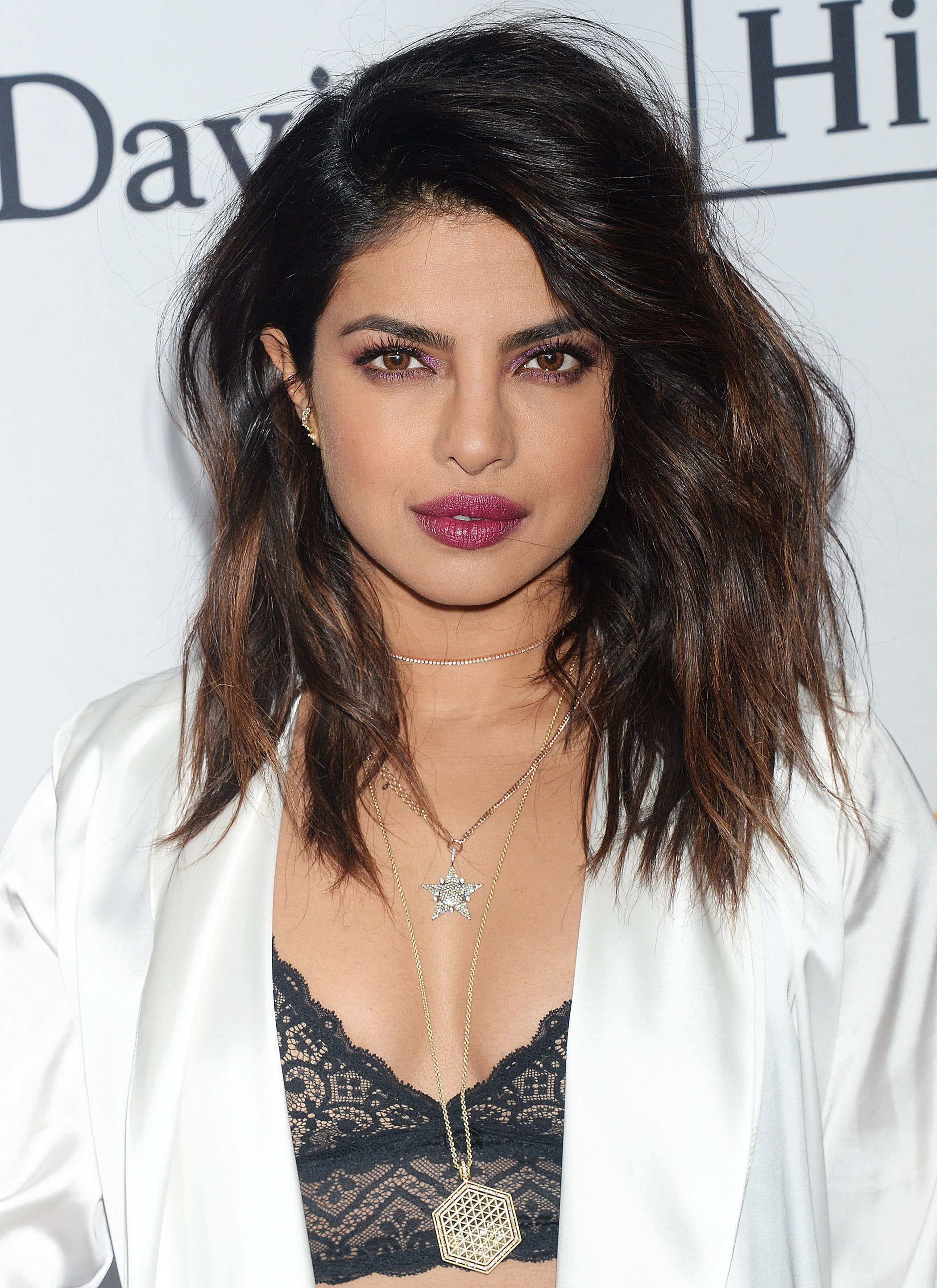 Shoulder length layered hair: Priyanka Chopra with mid-length brunette hair with highlights and layers, styled in a side parting