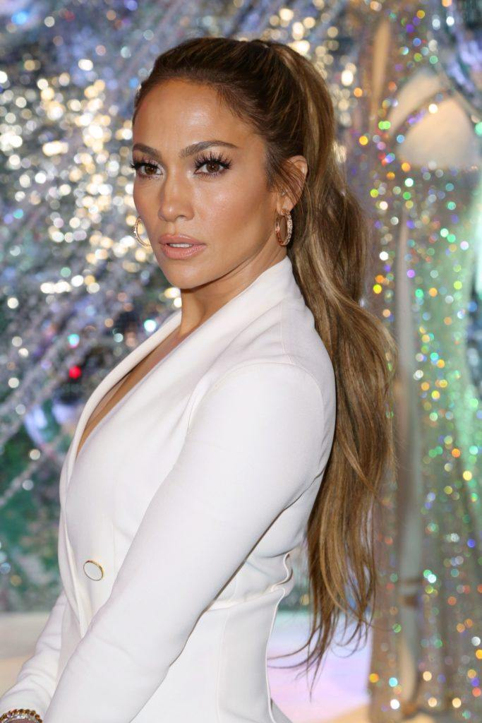Jennifer Lopez in 2017 with a highlighted long, high ponytail wearing a white suit