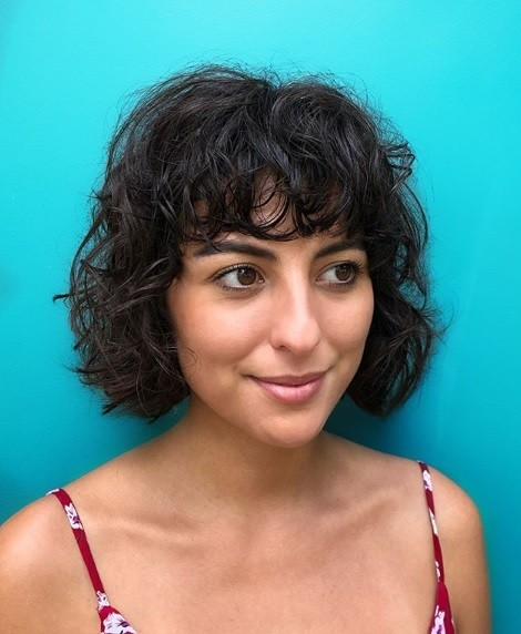 Brunette with a short shaggy wavy perm bob with a fringe, standing in front of a blue backdrop.