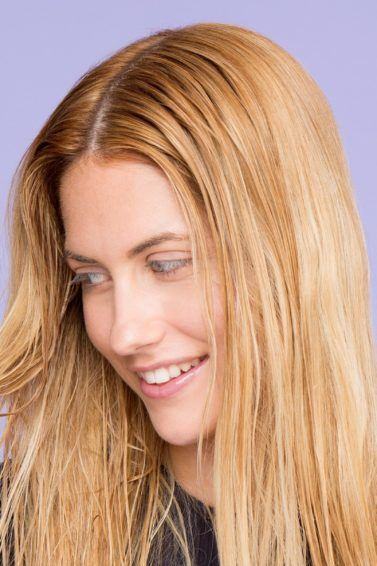 Shampoo full guide: Woman touching her straight blonde hair.