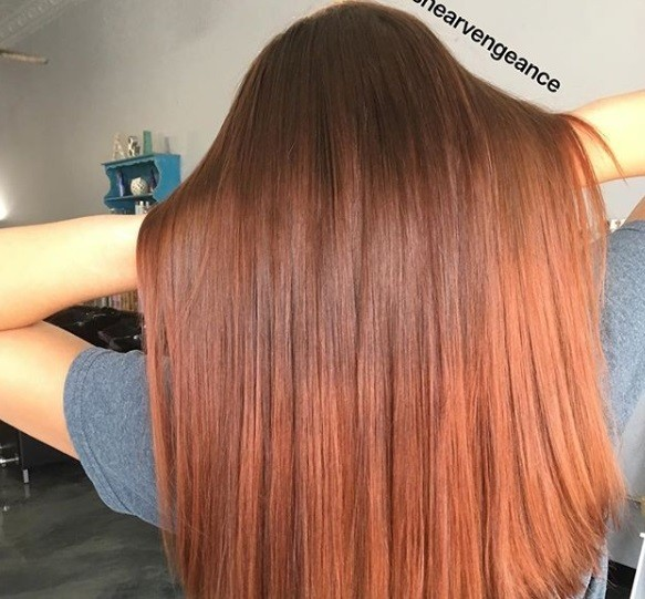 Red brown hair: Close up shot of a woman with long medium brown to ginger ombre hair.