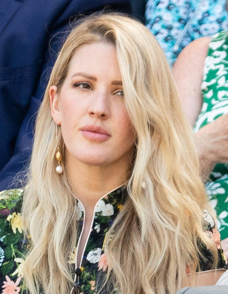 Ellie Goulding at Wimbledon 2018 with her long light blonde hair styled in beach waves sitting courtside ina floral dress
