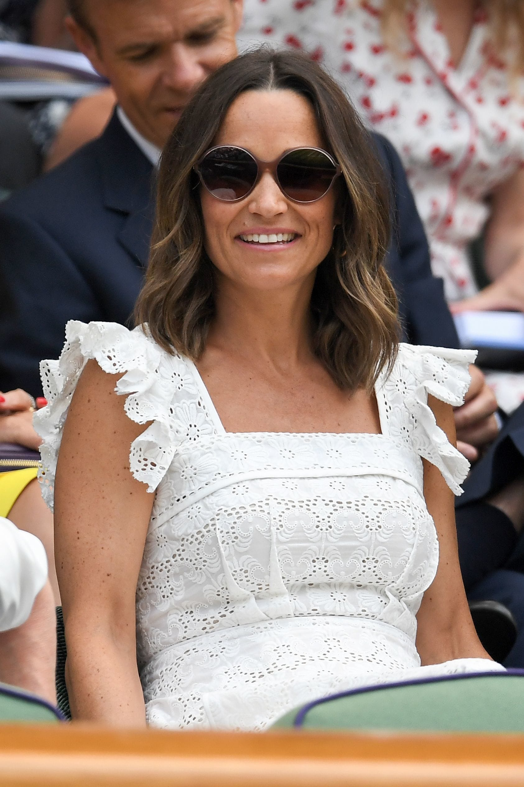 Pippa Middleton sitting courtside at Wimbledon 2018. Pippa is wearing a white dress with her shoulder-length brown highlighted hair styled in a wavy lob