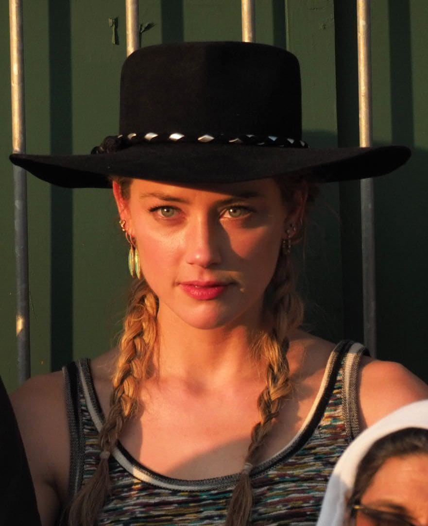 Amber Heard at Wimbledon 2018 with her blonde hair styled in two single braids wearing a black round hat