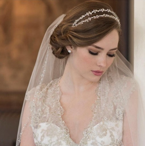 brunette bride with her hair in a side chignon with a wedding veil