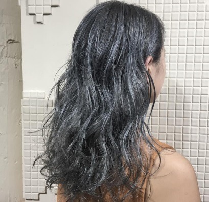 Back view of a woman with long silver grey permed curly hair.