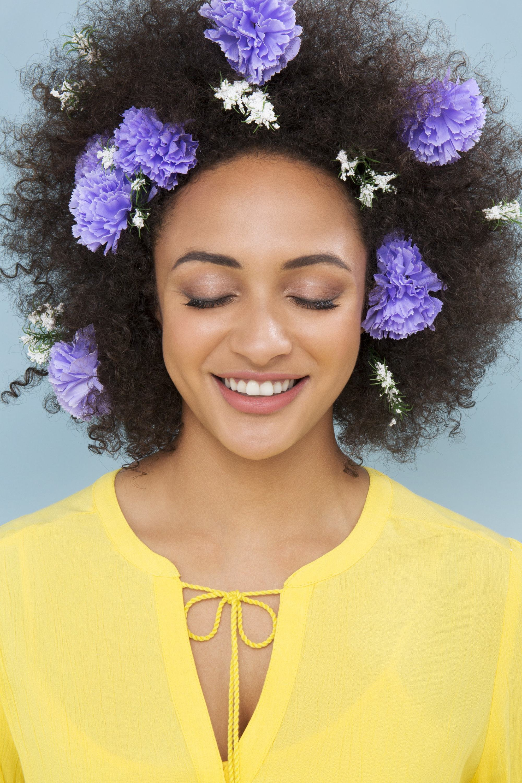 head shot of model with big afro with flowers in it wearing yellow
