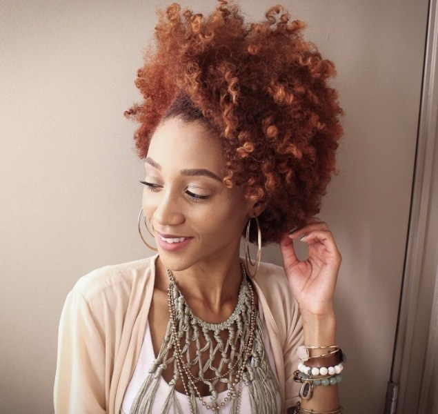 woman with strawberry blonde afro hair styled into a updo, wearing white shirt and jewellery