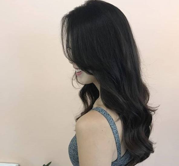 Loose perm: Close up shot of a woman with long dark brown layered loose perm hairstyle