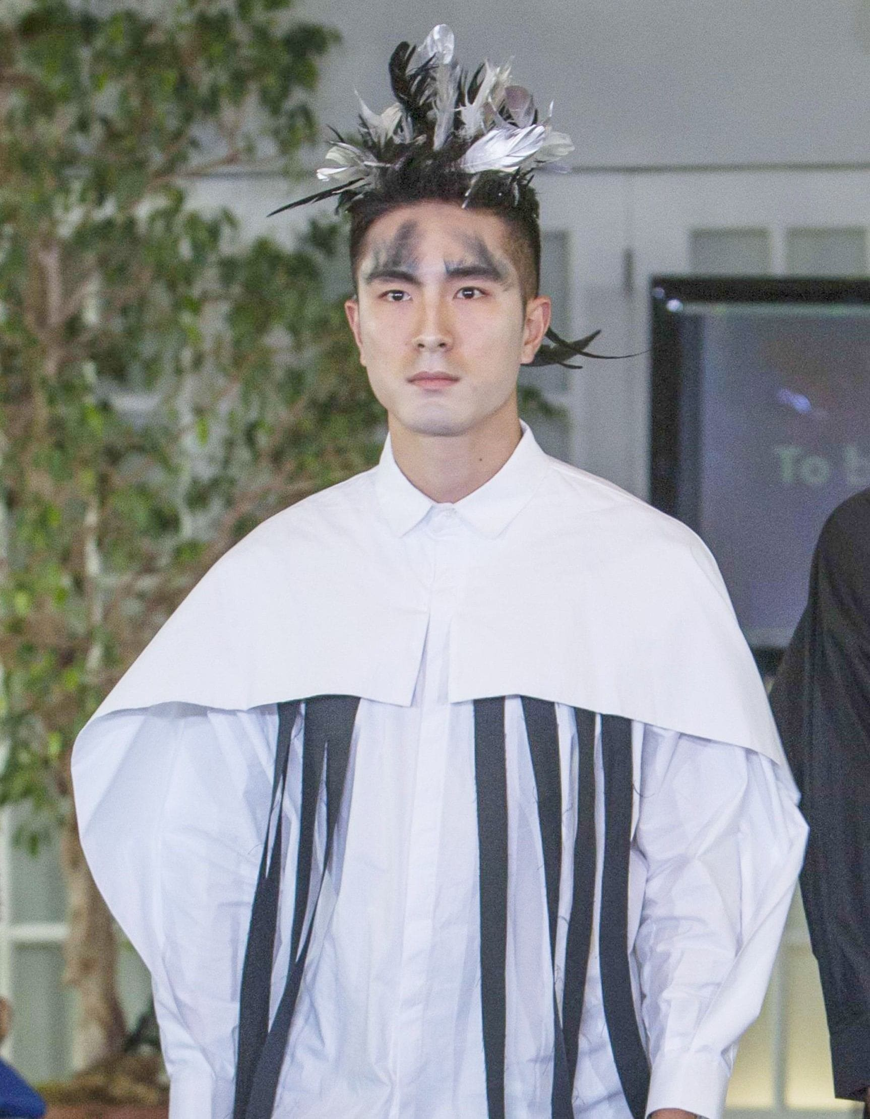 asian male model at the nyfw mens to be thrill show with feathers in his hair