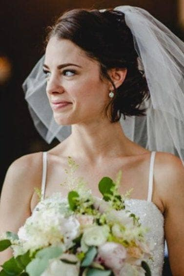 brunette bride with short bob length hair in a half up hairstyle wearing a lace veil and holding a bouquet