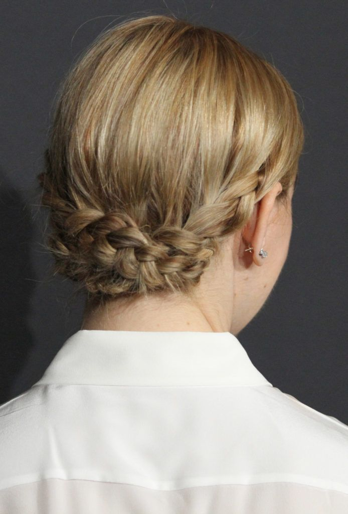 back view of zosia mamet with blonde hair styles in a low braided updo wearing a white short