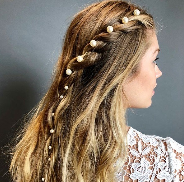 down prom hairstyles: close up shot of a woman with bronde hair with an accessorised accent braid, wearing a white floral top and posing outside