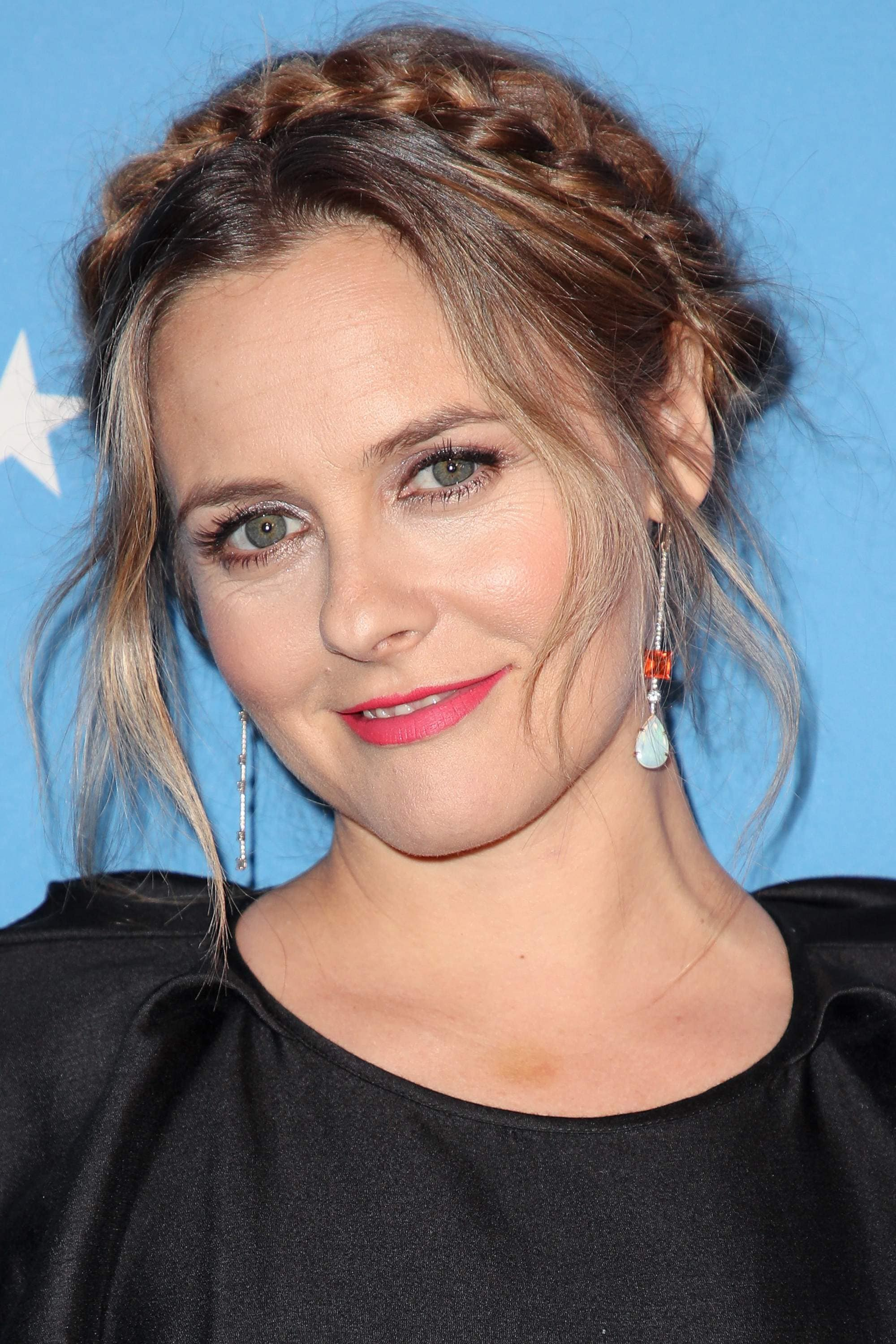 prom updos: actress Alicia Silverstone with her light brown hair in a wispy milkmaid braid style