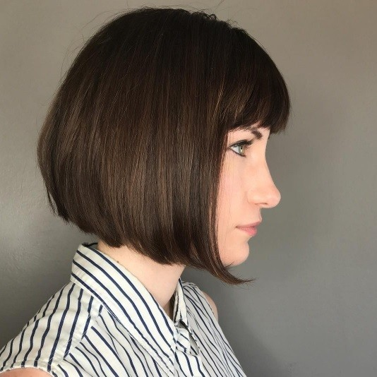 side profile of a brunette woman with an aline bob and bangs