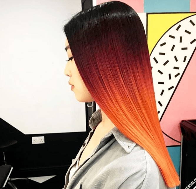side shot of woman with sunrise red highlights in her hair at a salon