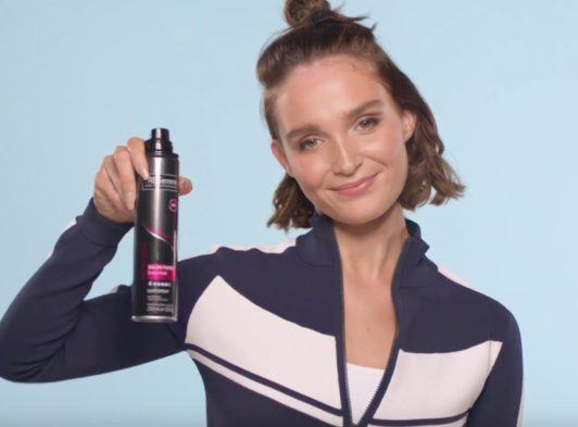 brunette blogger lissy roddy holding a can of hair spray smiling