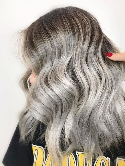 Ash blonde ombre: Close-up photo of a woman with shoulder-length wavy ash grey silver hair