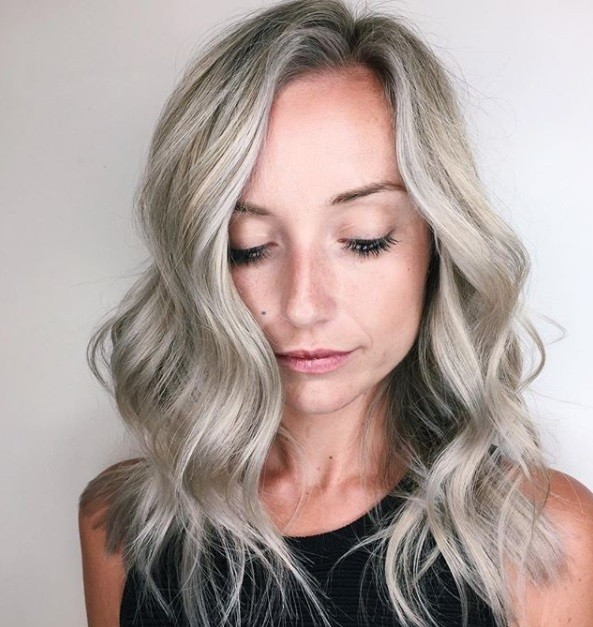 shot of woman at the salon with ashy silver and blonde hair that's been styled into waves