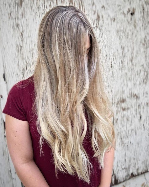 Ash blonde ombre: Photo of a woman with long vanilla blonde wavy hair, wearing a maroon t-shirt