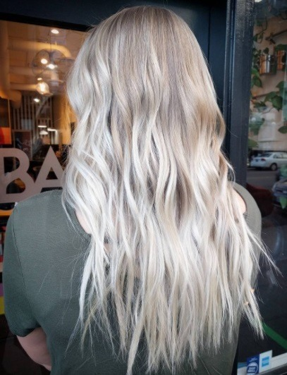 back view of a woman with long tousled light blonde ombre hair