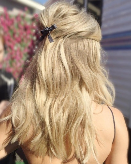back shot of a woman with blonde hair in a half up bouffant hairstyle