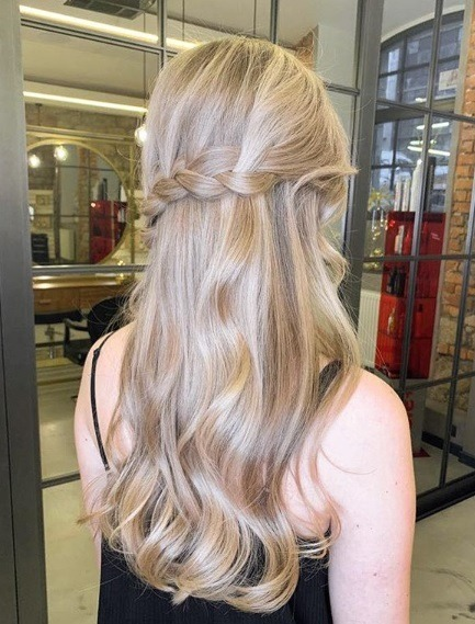 Ash blonde ombre: Back view of a woman with long beige blonde wavy hair styled in a twisted half-up half-down