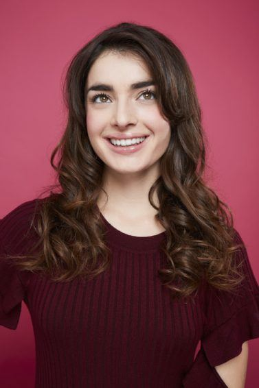 All Things Hair: Woman with romantic long brown curly hair, wearing purple jumper and posing against a pink background