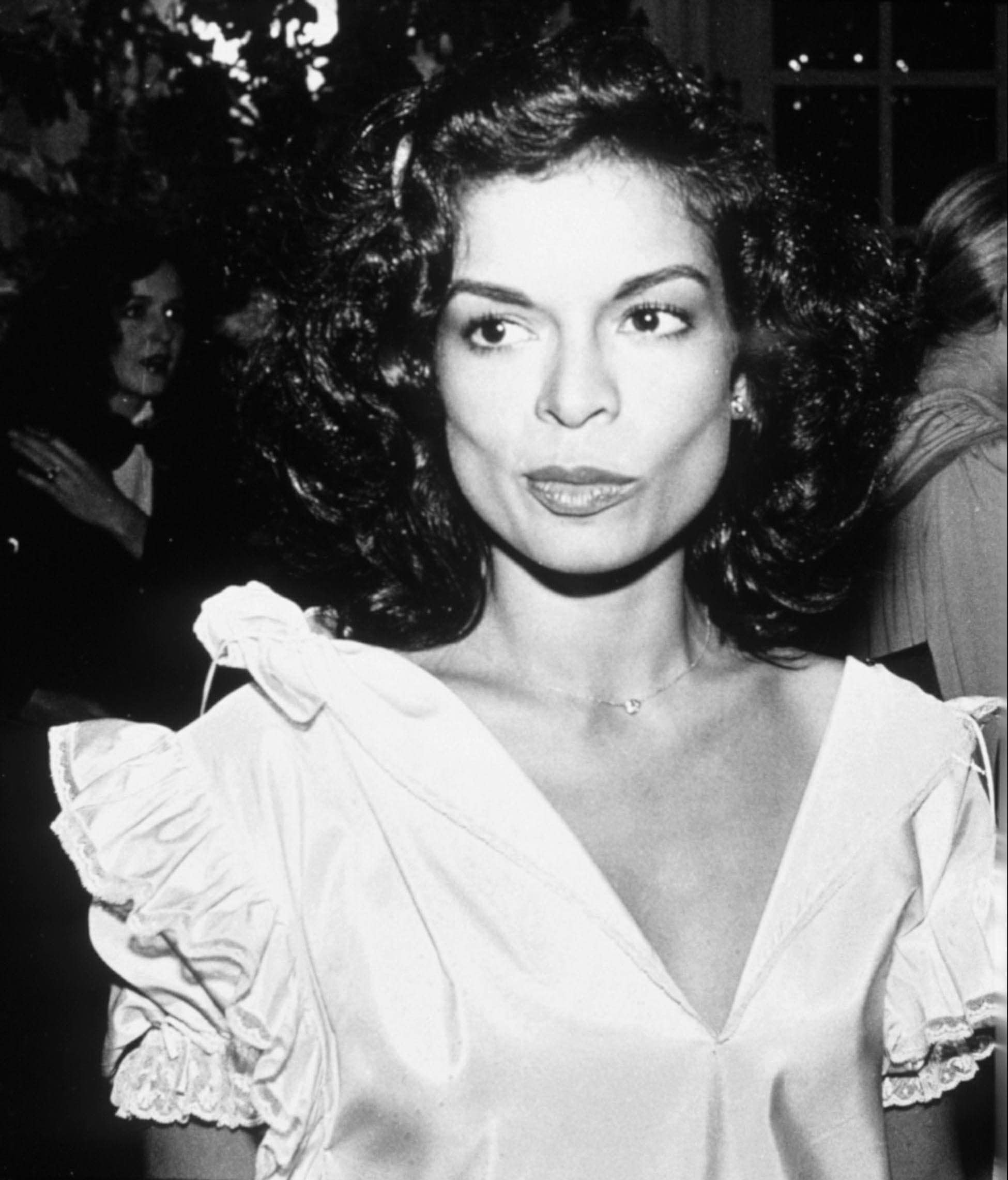 70s hairstyles: Bianca Jagger dark brown shoulder length hair with curls in black and white image wearing a white dress with puff sleeves