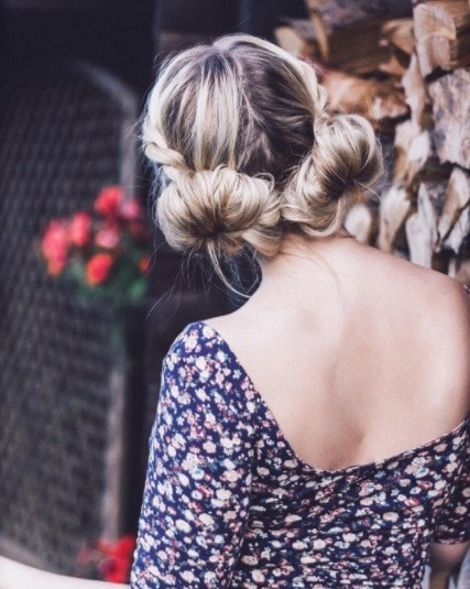 back view of a woman wearing a floral dress with her hair in big macaron bunsZDW