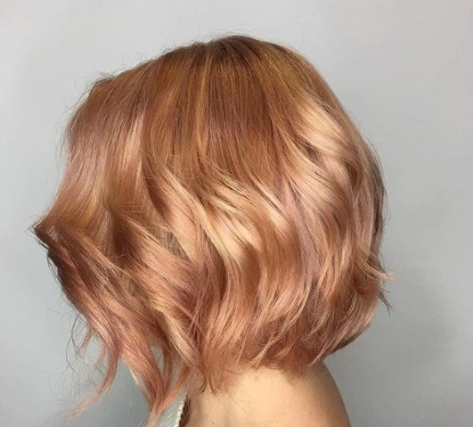 side shot of woman with blonde and red hair that's been waved at a salon