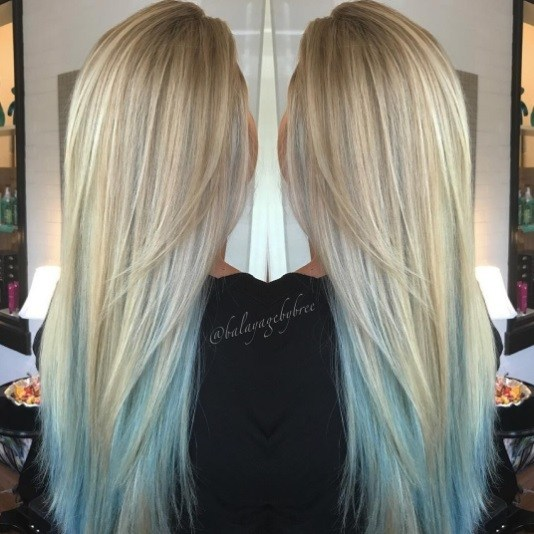 back view of a woman with long straight blonde hair with blue ombre