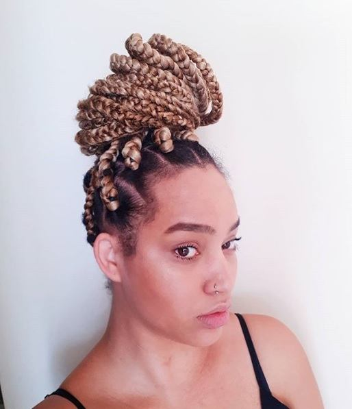 Long box braids hairstyles: Woman with golden box braids in a high top knot bun