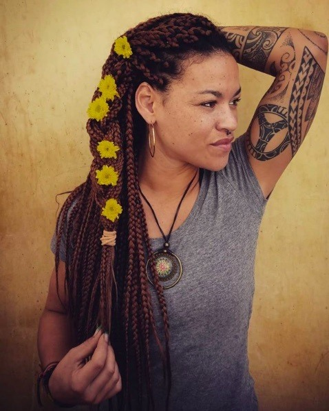 Long box braids hairstyles: Woman with red brown long box braids in a half-up braid with yellow flower accessories