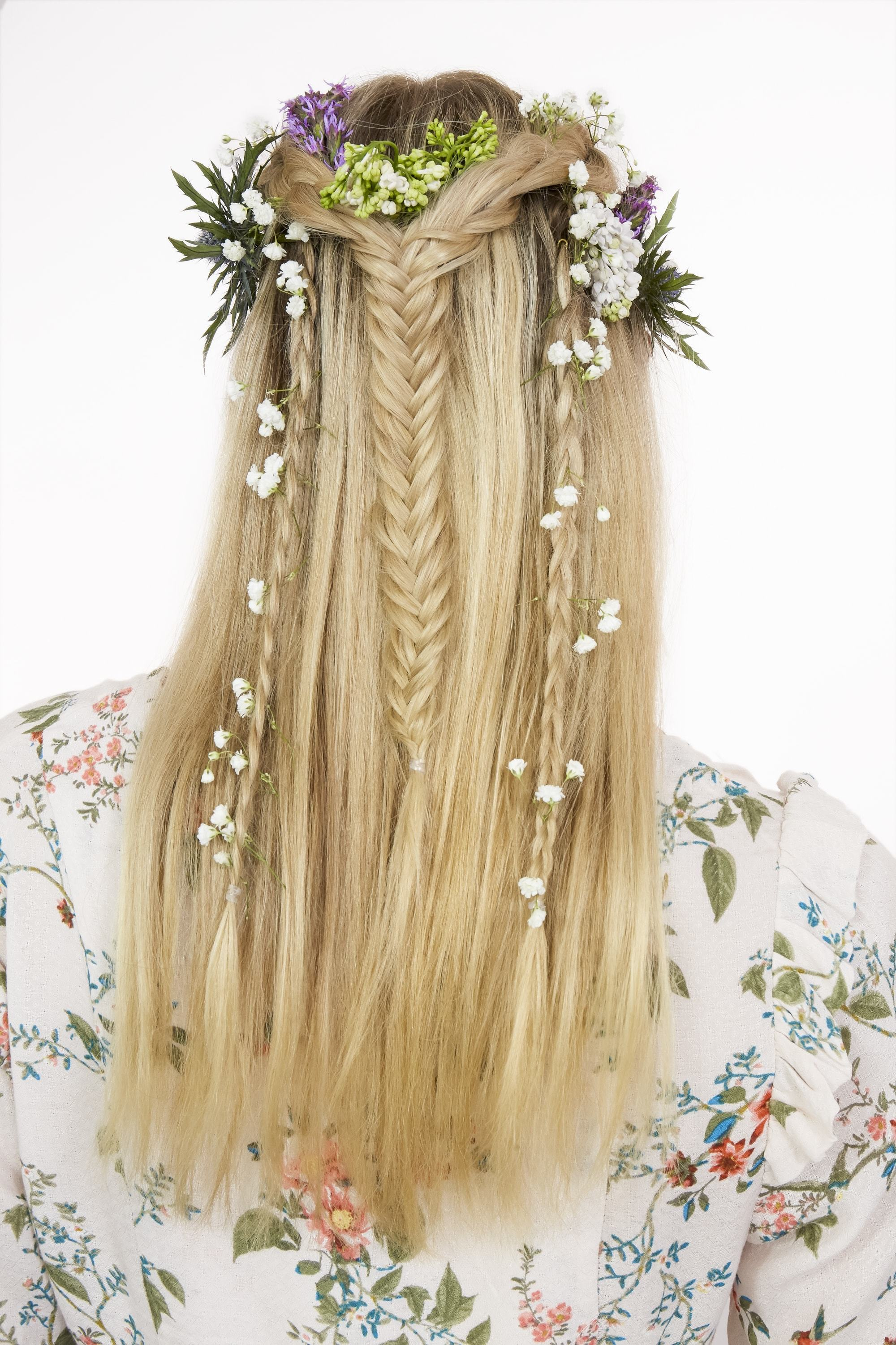 Braids for long hair: Woman with long straight highlighted blonde hair with fishtail braid half-up half-down adorned with flowers.