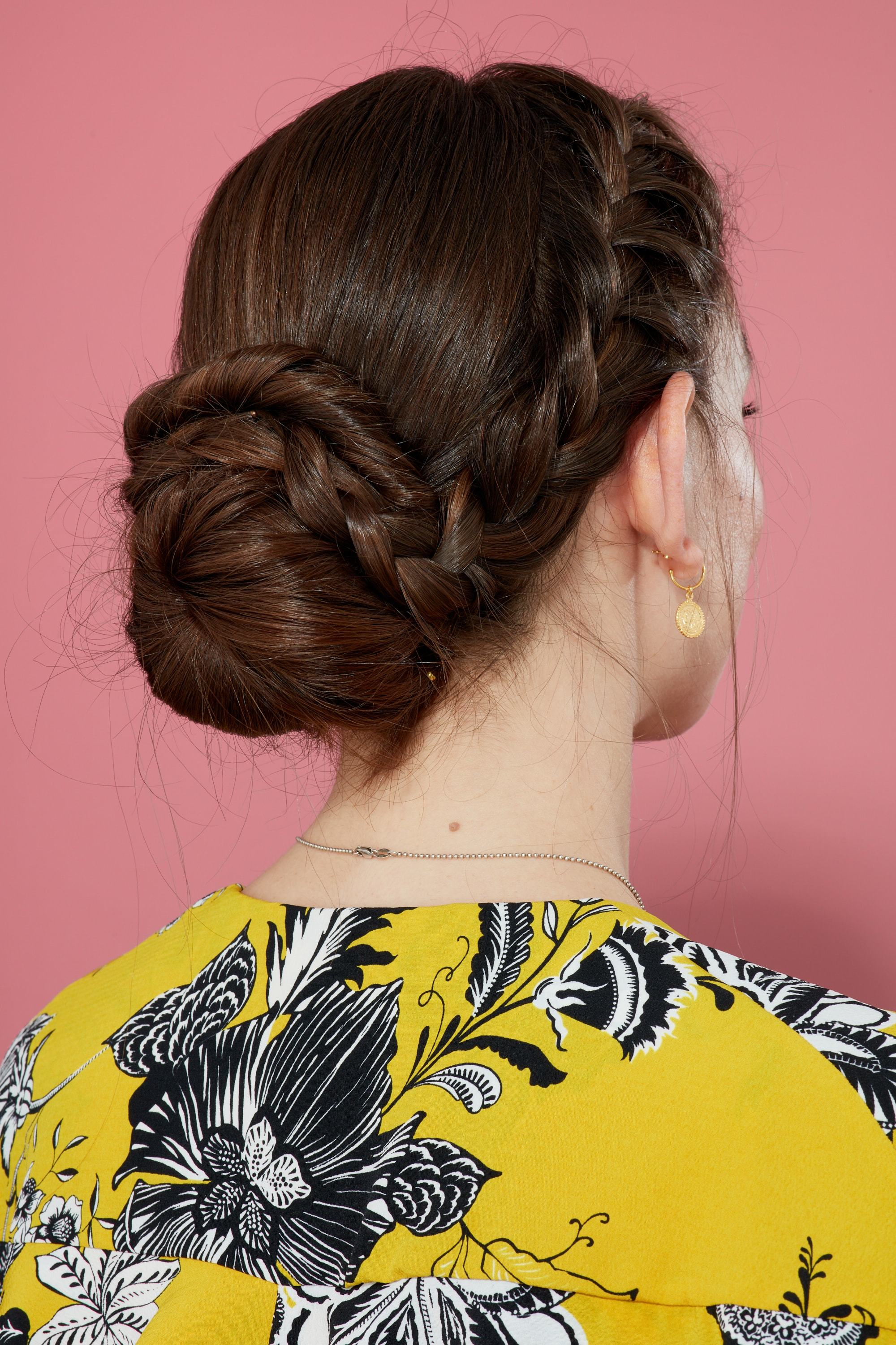 Braids for long hair: Woman with long brown hair in french braided bun wearing yellow pattern top against a pink backdrop.