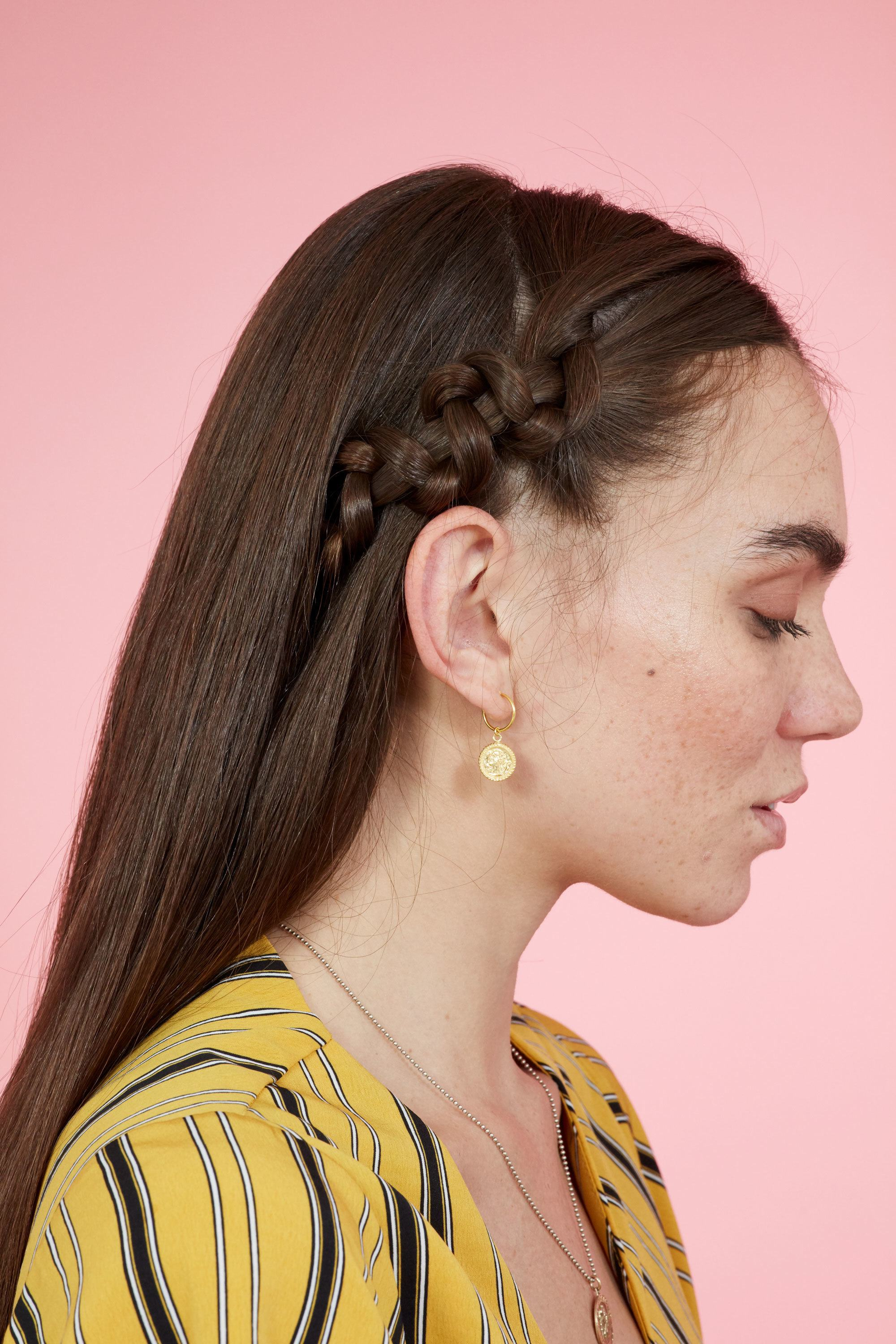 Braids for long hair: Woman with straiht dark brown hair with accent snake braid on one side wearing a yellow top against a pink backdrop.