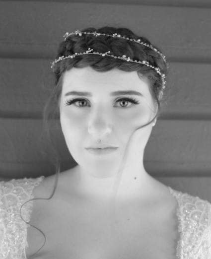 black and white face on photo of a bride with her dark hair in a crown braid updo with a crystal headpiece