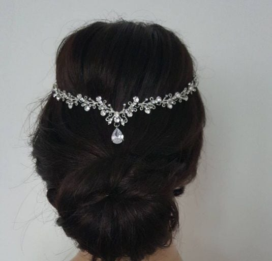woman with dark brunette hair in an updo style with a crystal headpiece