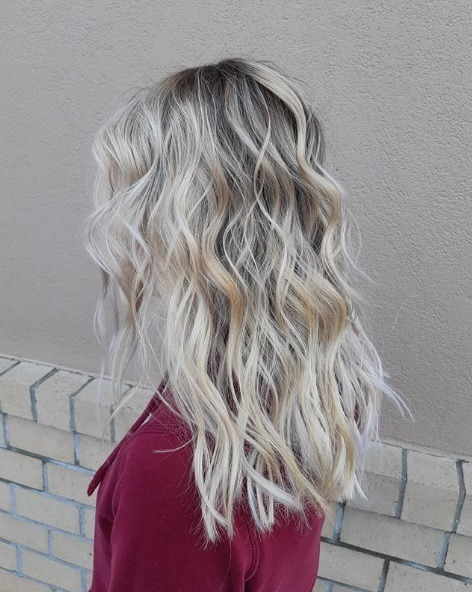 Ash blonde ombre: Side profile of a woman with champagne ash blonde highlihted hair, styled in loose curls, wearing a berry coloured top