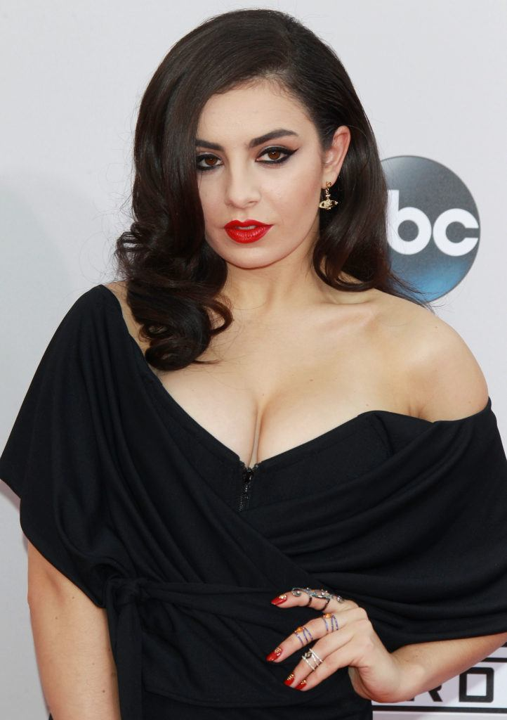 Charlie XCX wears her black hair in side parting with glamorous waves and black off the shoulder dress at American Music Awards 2014