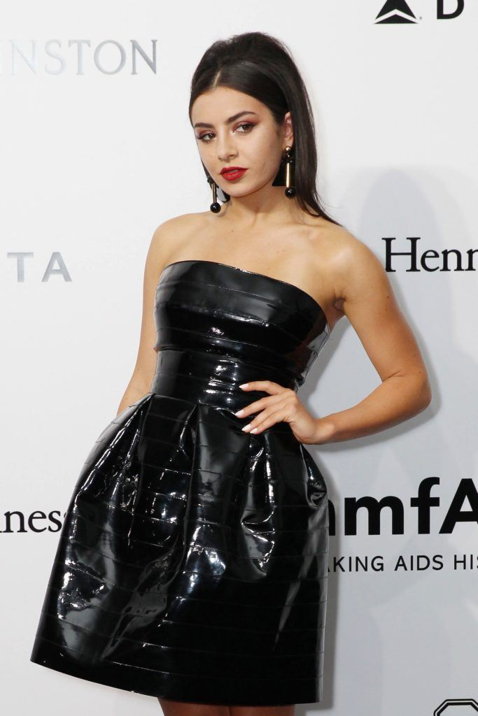 Charli XCX wears her black hair in high bouffant ponytail with front section smoothed back the look is finished with a black strapless dress