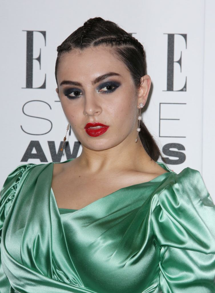 Charli XCX wears her black hair with three braids tied into low ponytail with bold makeup and green dress ar the Elle Style Awards 2016