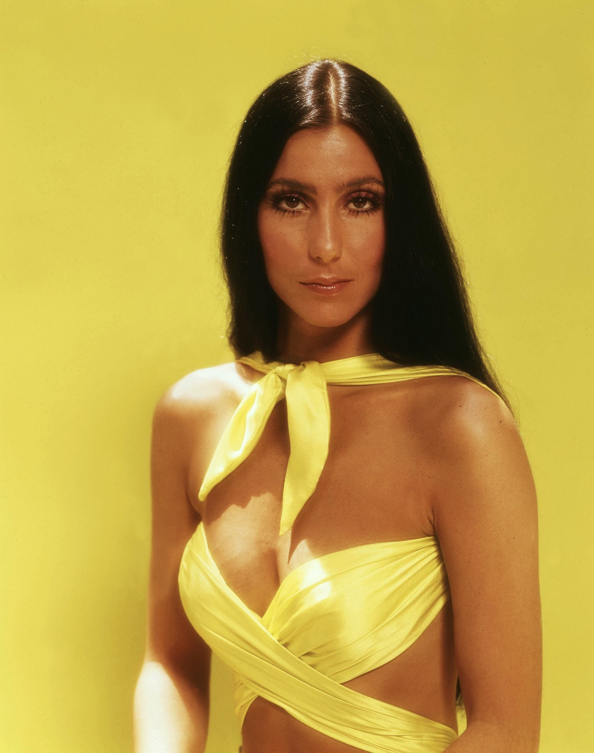 70s hairstyles: Cher with long dark brown glossy straight hair wearing a yellow cut out dress pictyred in front of a yellow backdrop