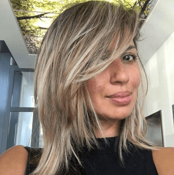 shoulder length ash brown hair with blonde toned chunky highlights swept across the face