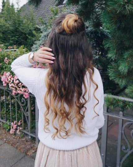 woman standing by a fence in front of some trees with her long ombre hair in a half up bun hairstyle