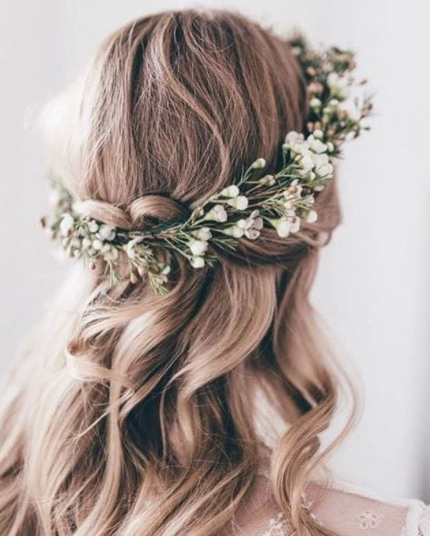 Blonde hair in crown braid half-up, half-down hairstyle with floral detailing