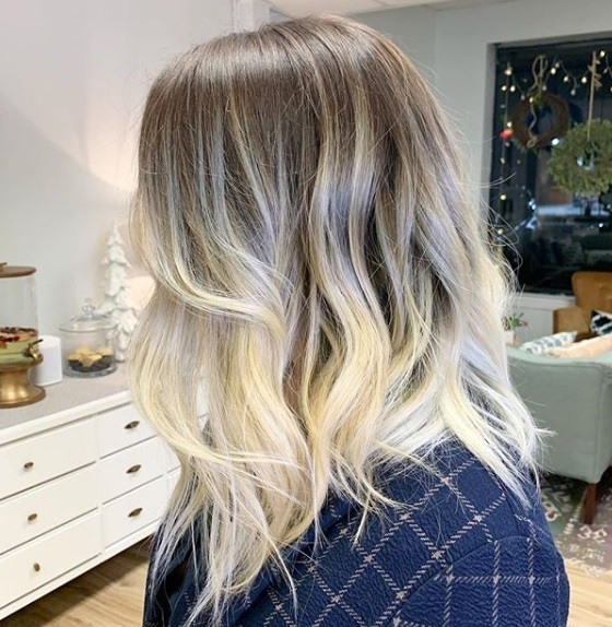 Ash blonde ombre: Side view of a woman with mid-length brown to blonde sombre hair styled in soft waves, wearing a plaid shirt